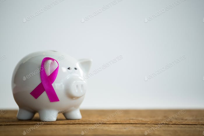 Close-up of pink Breast Cancer Awareness ribbon on piggybank over wooden table