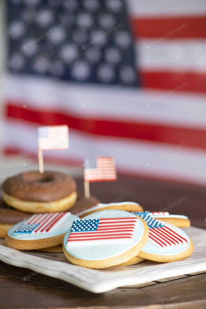 Hausgemachte Schokoladen-Donuts und Kekse vor der amerikanischen Flagge für die US-Nationalfeiertage