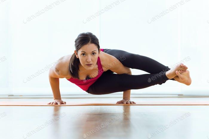 Hermosa mujer joven practicando yoga en casa.