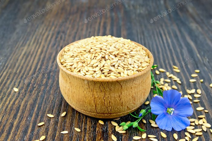 Flaxen white seed in bowl with flower on board