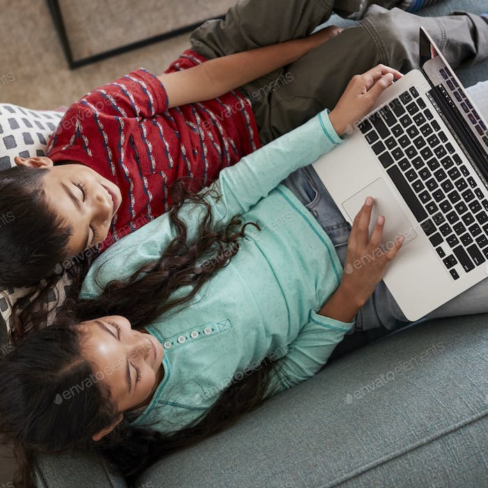 Overhead View Of Brother And Sister Sitting On Sofa At Home Having Fun Playing On Laptop Together