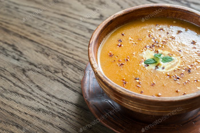 Bowl of spicy pumpkin cream soup on the wooden table