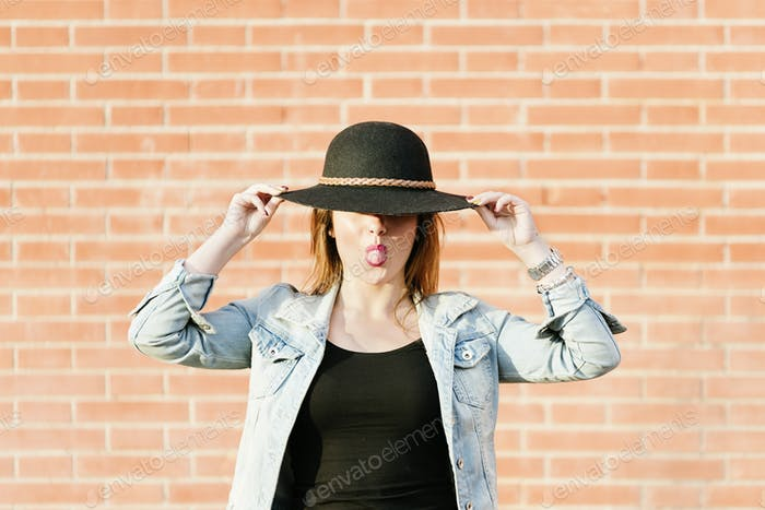 Blonde hipster posing with straw hat against orange brick background.