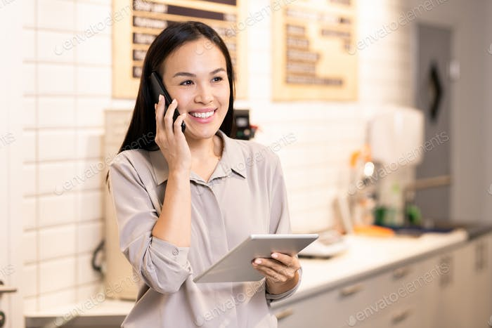 Young cheerful manager of restaurant communicating with client on mobile phone