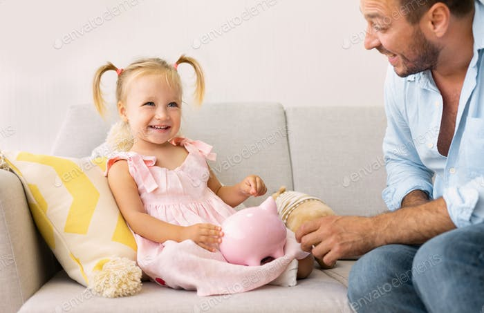 Dad teaching his child how to save money