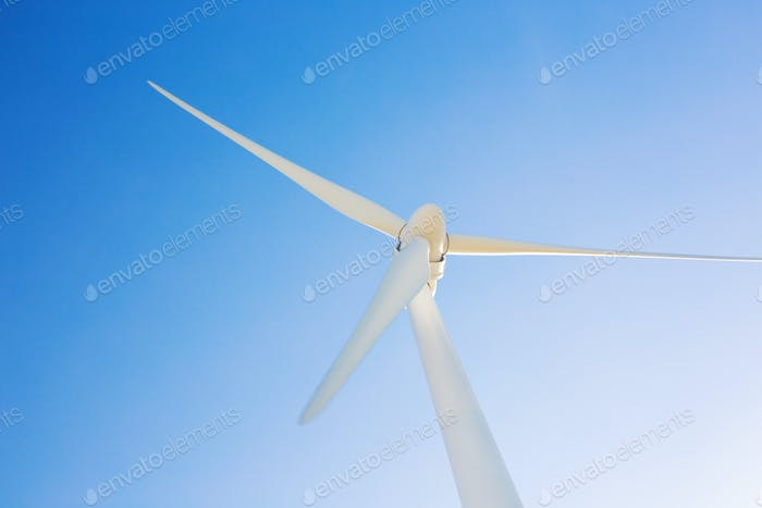 Wind turbine generating electricity with blue sky - energy conservation concept