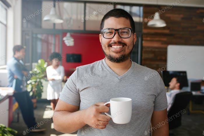 Lächelnd kreative Profi mit Kaffee im Büro