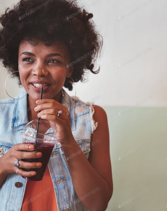 Young african woman drinking fresh fruit juice
