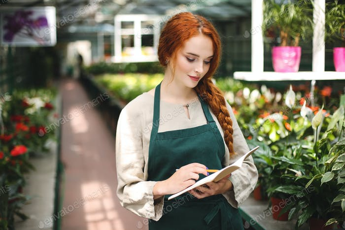 Beautiful florist in apron standing with pencil in hand and dreamily writing in notepad