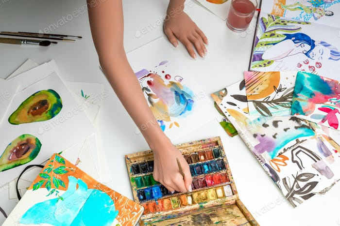 selective focus of female hands mixing watercolor paints surrounded by color pictures