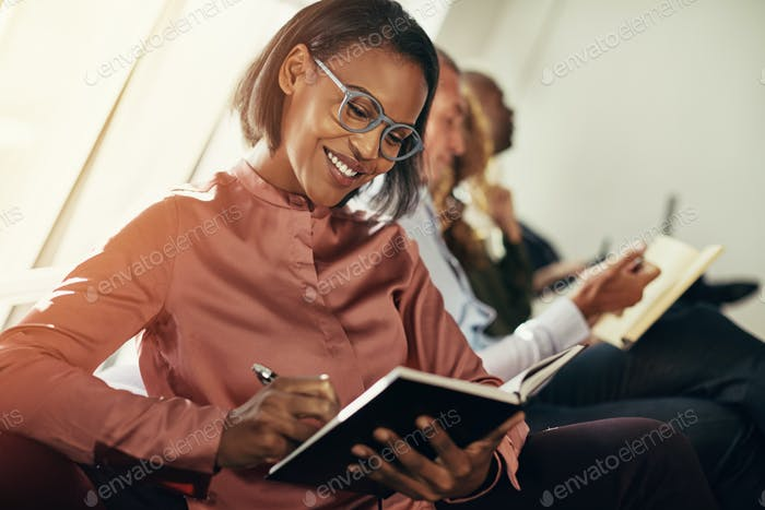 Smiling African businesswoman taking notes during an office presentation