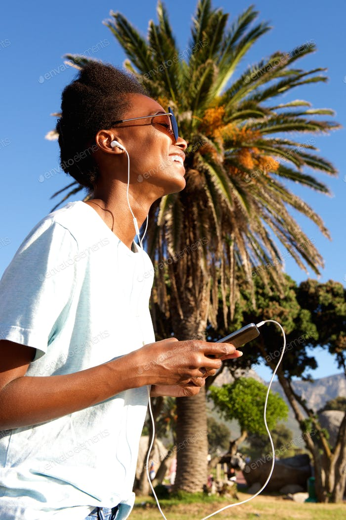 Happy young woman listening to music on beach