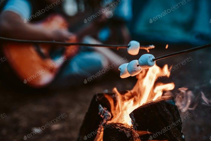 Toasten von Marshmallow auf den Scheiterhaufen und Gitarrist im Wald