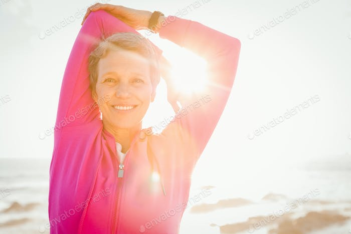 Portrait of smiling sporty woman stretching arms at promenade on a sunny day