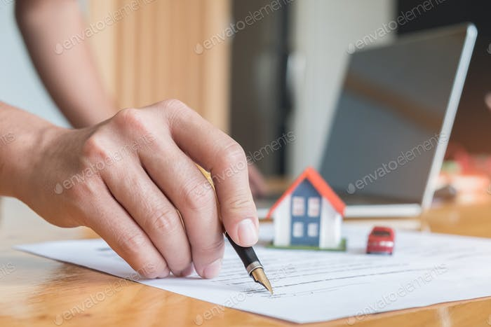 Pen handles signed documents with model houses.