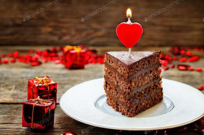 chocolate cake with candles in the shape of a heart