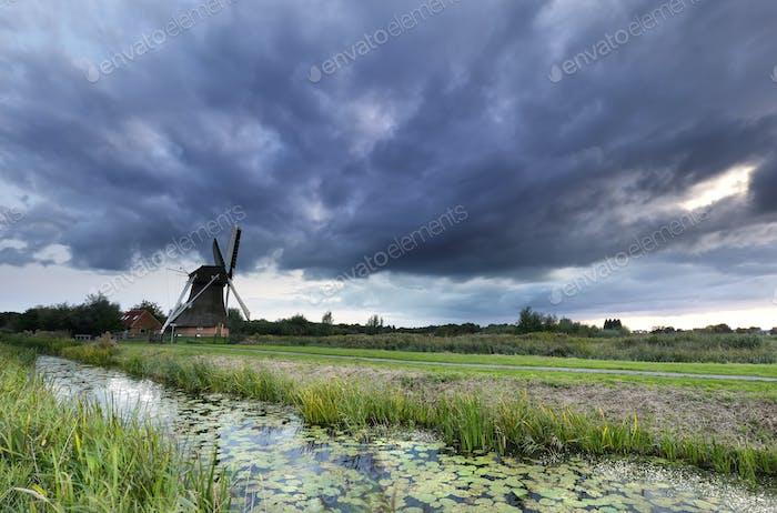 dark shower clouds over Dutch windmill