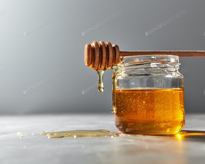 Dripping organic natural fresh honey from glass pot on a gray kitchen table. Rosh hashanah jewish