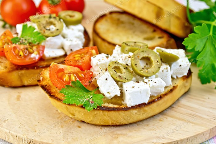 Sandwich with feta and olives on wooden board