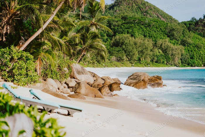 Sun lounger at secluded tropical beach. Ocean waves rolling to shore with white sand and coconut