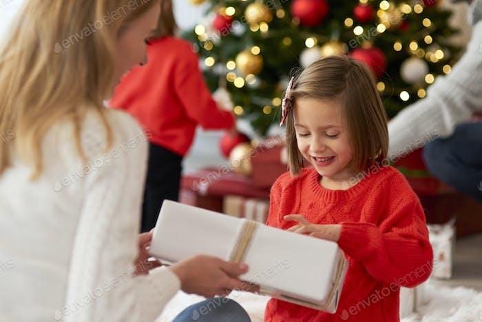 Familie beginnt Weihnachten von Eröffnungsgeschenken