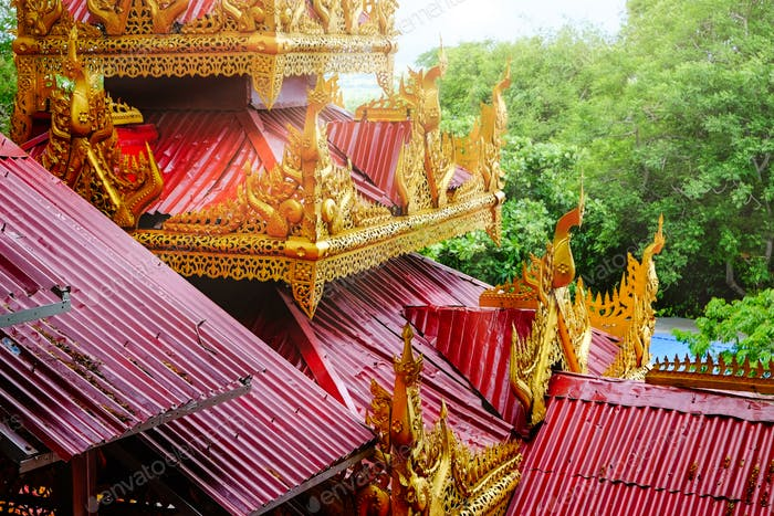 Architectural detail of colorful red and gold roofs on a temple