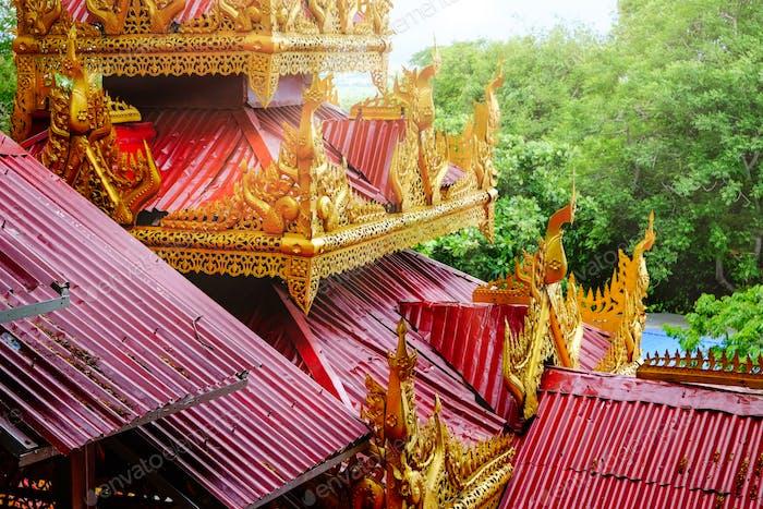 Architektonisches Detail der bunten roten und goldenen Dächer auf einem Tempel