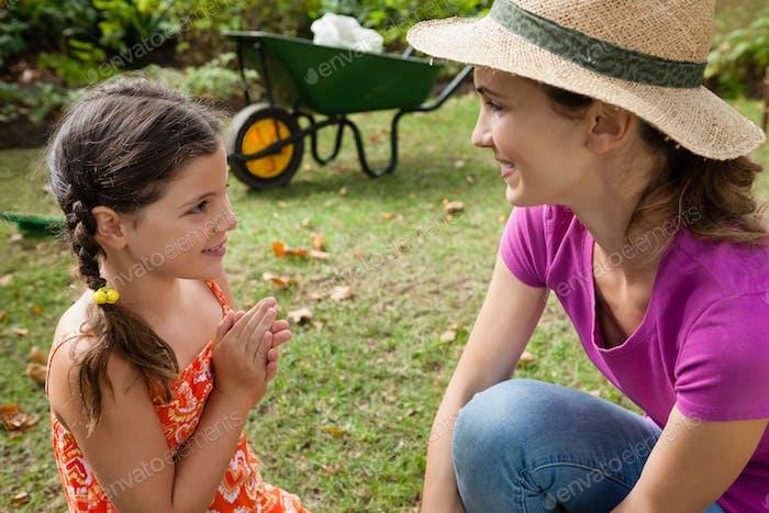 Lächelnde Mutter und Tochter im Gespräch auf Feld