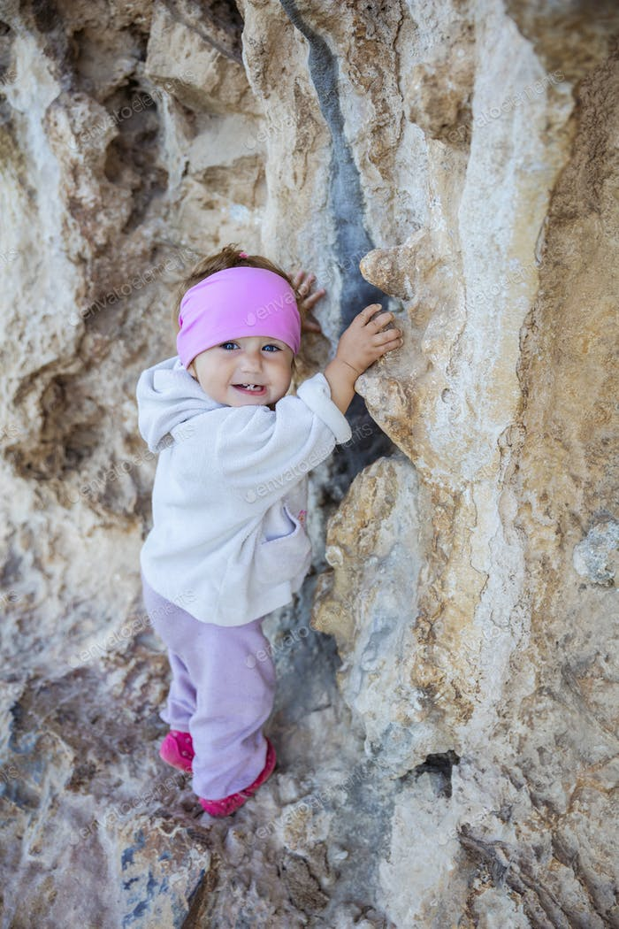Little girl playing on rocks near climbing sector