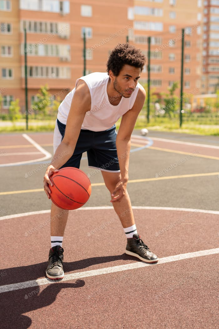 Young basketballer in activewear bending forwards before throwing ball