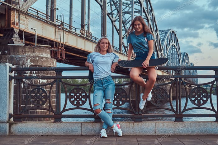 Two happy young hipster girls leaning on a guardrail on a background of the old bridge.