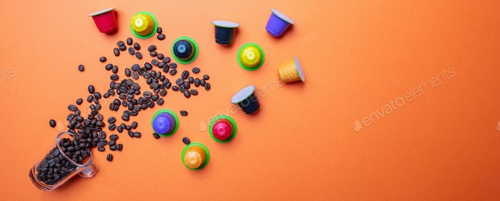Coffee beans and capsules on orange color background, banner