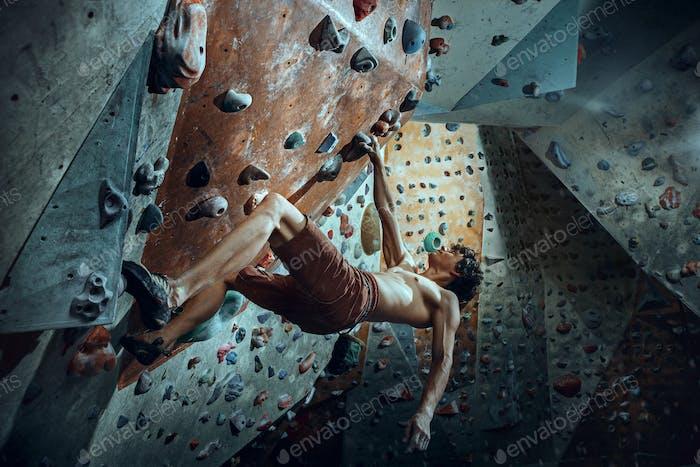 Free climber young man climbing artificial boulder indoors