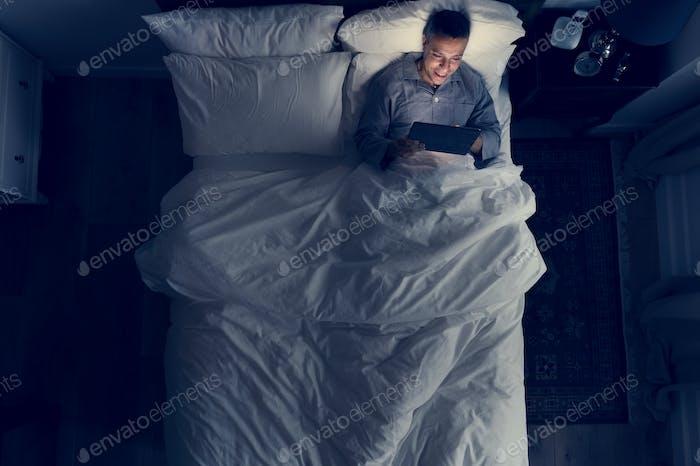 Mann im Bett mit seinem Tablet