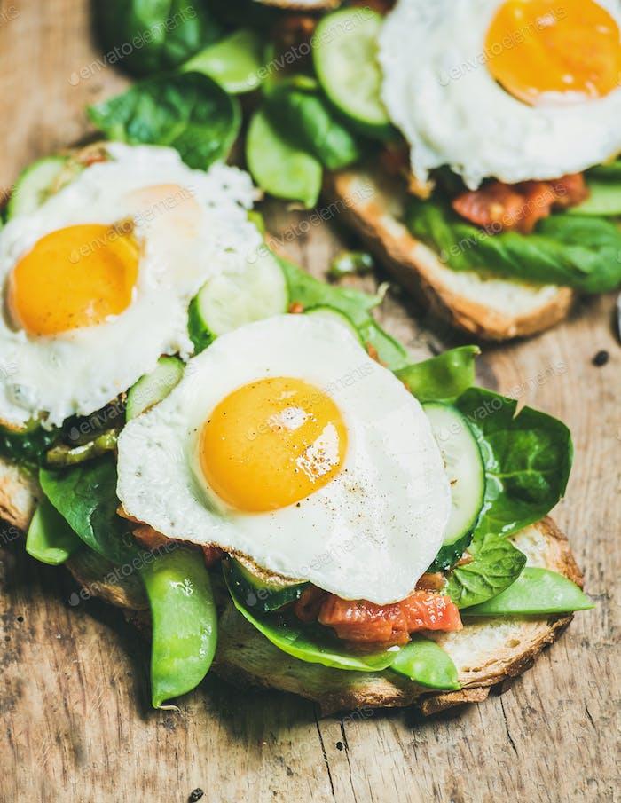 Healthy breakfast sandwiches on wooden board background
