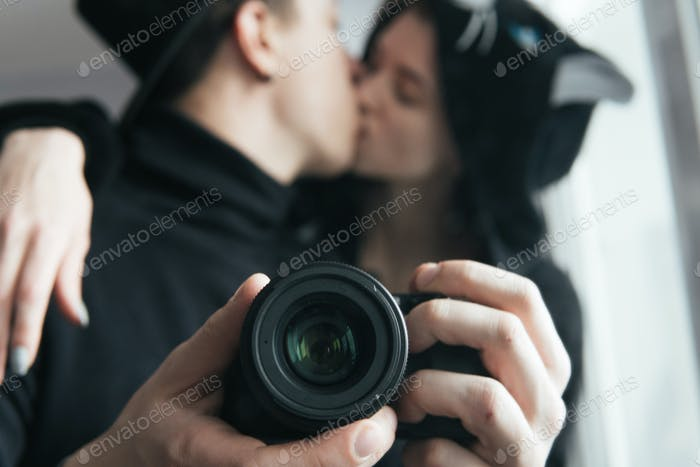 man and woman in black clothes kissing