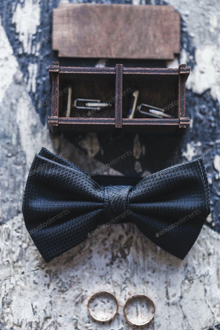 Groom wedding accessories, bow tie, cufflinks in wooden box, rings