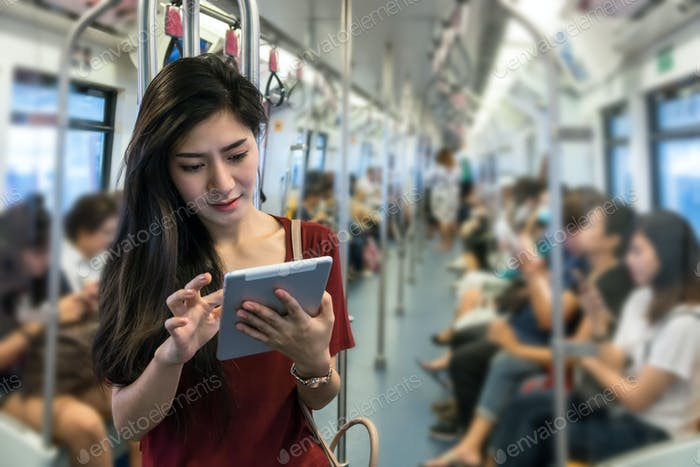 Asian woman passenger with casual suit using the technology tablet in the BTS Skytrain rails