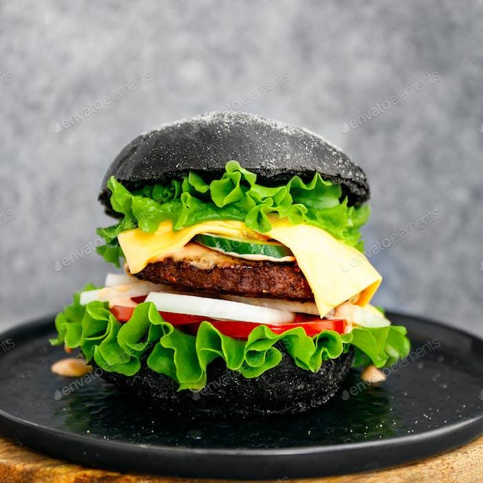 Großer schwarzer Burger mit Marmor Rindfleisch Pastetchen, Käse und frischem Gemüse