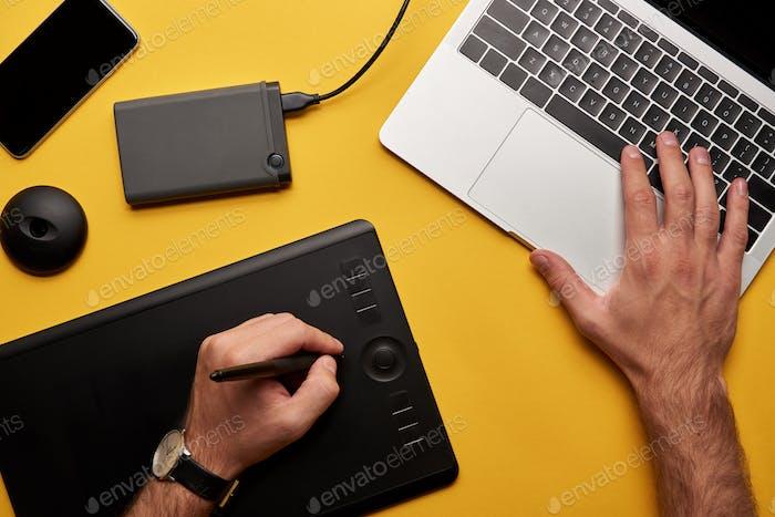 foto recortada del diseñador Gráficos que trabaja con portátil y tableta gráfica en superficie amarilla