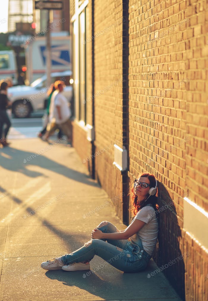 Girl with headphones near the wall