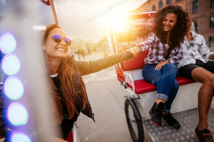 Best friends enjoying tricycle ride in the city