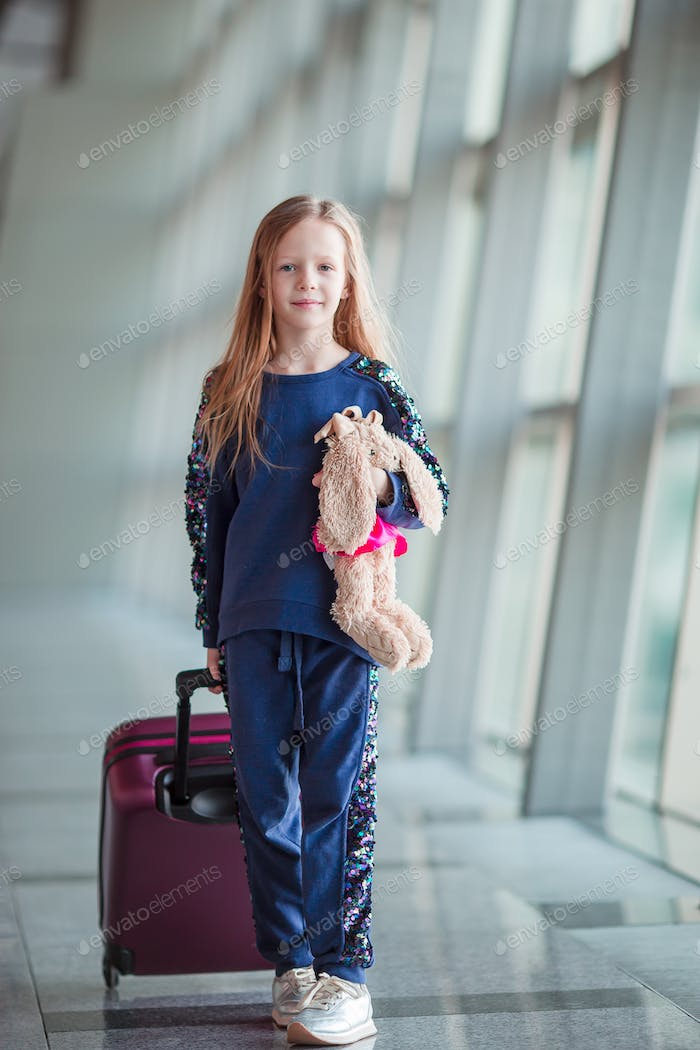 Adorable little girl in airport with her luggage waiting for boarding