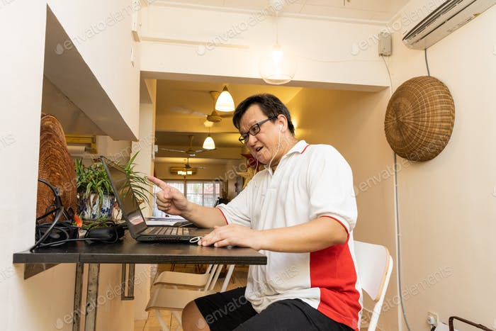 Matured Asian business man work from home expressing himself during video conference