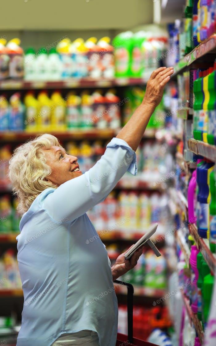 Mujer comprando detergentes para el hogar en la tienda