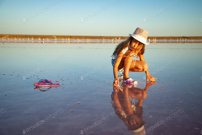 A little beautiful girl is looking at something in a transparent water surface on a transparent