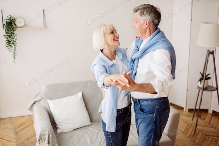 Happy mature couple dancing in the living room
