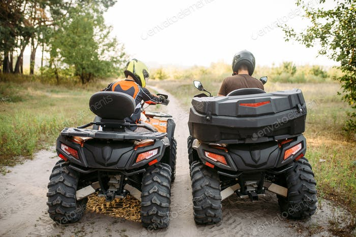 Two atv riders in helmets, back view, quad bike