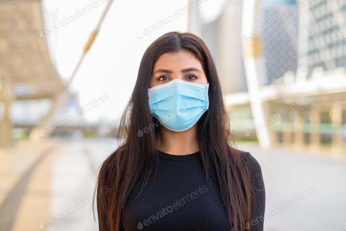 Face of young Indian woman with mask for protection from corona virus outbreak at the skywalk bridge