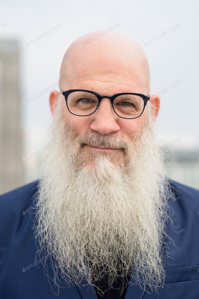 Face of mature handsome bald bearded businessman wearing eyeglasses outdoors